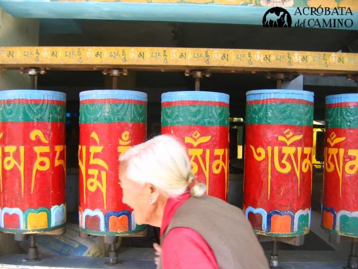 mujer tibetana gira las ruedas de plegarias