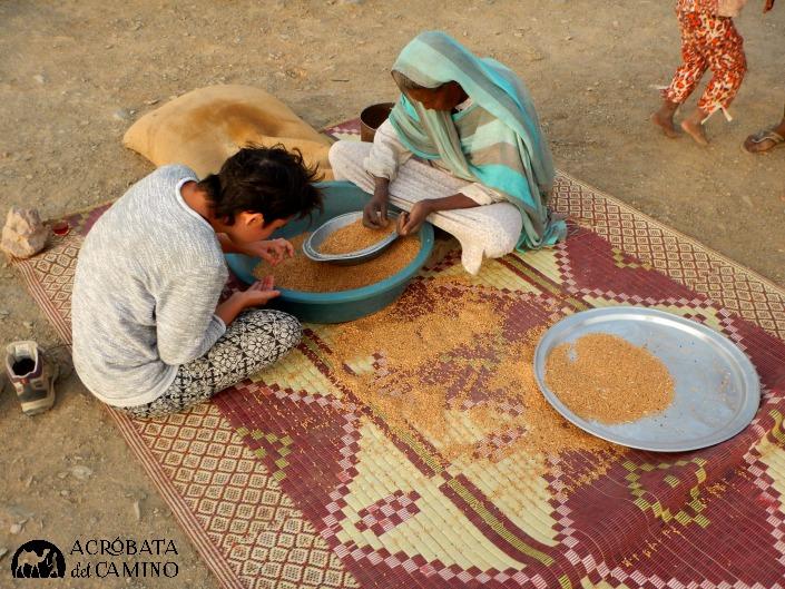 No se podrá arreglar el mundo, pero se pueden compartir simples momentos: Laura separa el trigo junto a una mujer en una aldea nubia en Sudán.