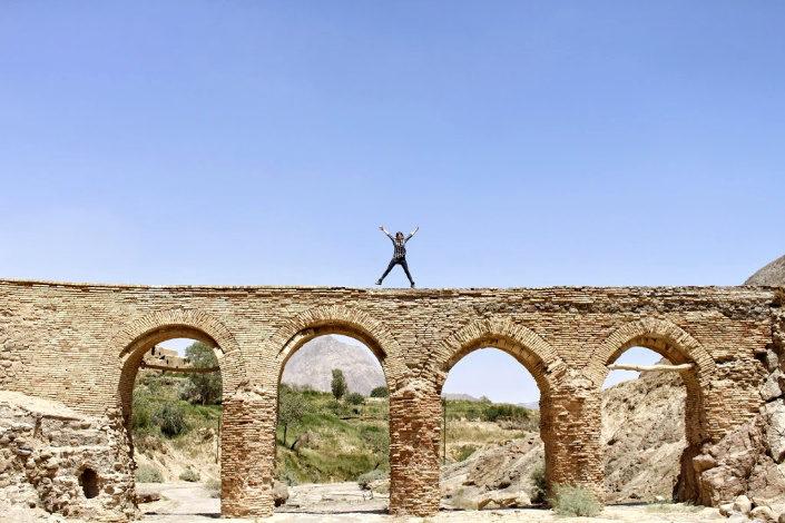 mujer saltando en un puente en Iran