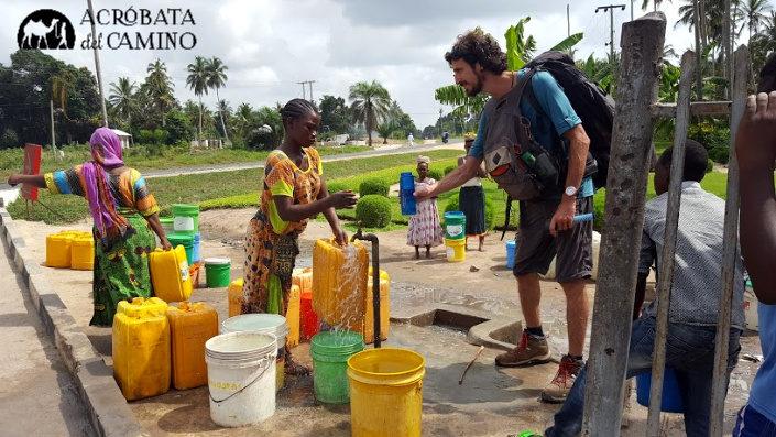 Mochilero cargando agua en una aldea rural en Tanzania